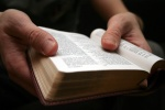 Image of hands holding an open Bible.